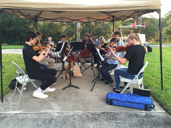 Former and current members of the FYO String Quartet(s) performing roadside, 2015.